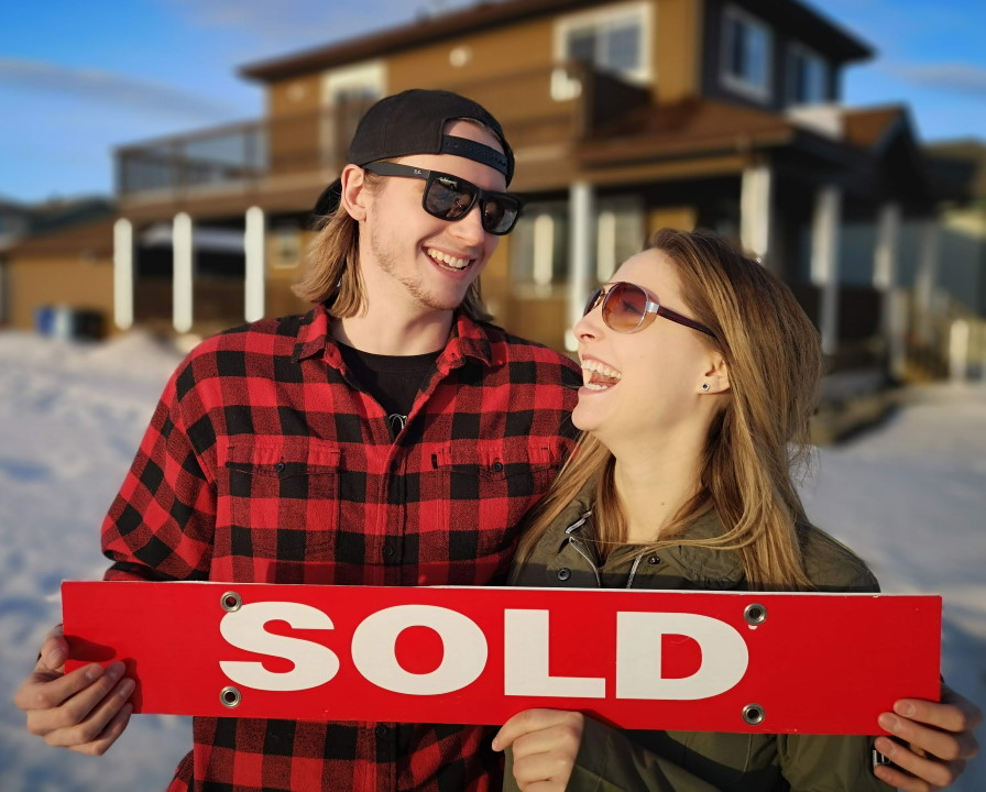 Photo of couple with sold sign